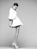 Schönheit mit den langen Beinen im weißen Kleid, im Pelz und in den hohen Absätzen, die im Studio aufwerfen Lizenzfreie Stockfotografie