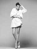 Schönheit mit den langen Beinen im weißen Kleid, im Pelz und im hohen Absatz Stockbild