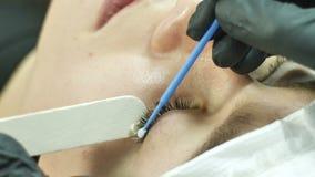Schönheit mit den langen Wimpern in einem Schönheitssalon Wimper-Erweiterungs-Verfahren stock footage