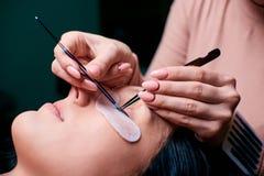 Schönheit mit den langen Wimpern in einem Schönheitssalon Wimper-Erweiterungs-Verfahren Peitschen schließen oben lizenzfreies stockfoto