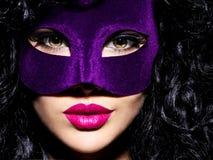Schönheit mit den schwarzen Haaren und violette Theatermaske auf fac Stockbild