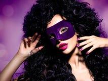 Schönheit mit den schwarzen Haaren und violette Theatermaske auf fac Lizenzfreie Stockfotografie