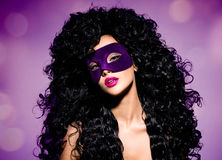 Schönheit mit den schwarzen Haaren und violette Theatermaske auf fac Stockfoto
