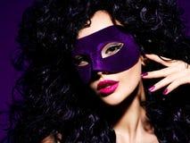 Schönheit mit den schwarzen Haaren und violette Theatermaske auf fac Stockfotografie