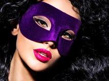 Schönheit mit den schwarzen Haaren und violette Theatermaske auf fac Lizenzfreie Stockbilder
