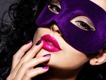 Schönheit mit den schwarzen Haaren und violette Theatermaske auf fac Lizenzfreie Stockfotos
