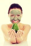 Schönheit mit der Gesichtsmaske, die Avocado hält Stockfotografie