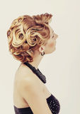 Schönheit mit der tragenden kleinen Schwarze des blonden Haares, die ihre Halsansicht von der Rückseite auf Weiß berührt Lizenzfreie Stockbilder