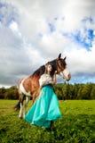 Schönheit mit einem Pferd auf dem Gebiet Mädchen an Stockfotografie