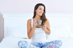 Schönheit mit einer Schale Morgenkaffee im Bett Lizenzfreies Stockfoto
