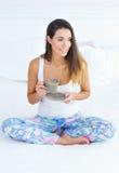 Schönheit mit einer Schale Morgenkaffee im Bett Stockbild