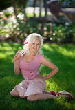 Schönheit mit Eiscreme draußen, Mädchenessen icecrea im Park, Sommerferien. Recht blond auf Natur. glückliche lächelnde Frau Lizenzfreies Stockfoto