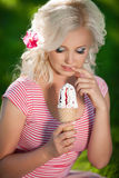 Schönheit mit Eiscreme draußen, Mädchenessen icecrea im Park, Sommerferien. Recht blond auf Natur. glückliche lächelnde Frau Stockfotografie