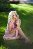 Schönheit mit Eiscreme draußen, Mädchenessen icecrea im Park, Sommerferien. Recht blond auf Natur. glückliche lächelnde Frau Stockfotos