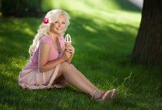 Schönheit mit Eiscreme draußen, Mädchenessen icecrea im Park, Sommerferien. Recht blond auf Natur. glückliche lächelnde Frau Lizenzfreies Stockbild