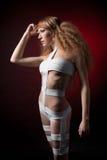 Schönheit mit gelockter Frisur gegen roten Hintergrund Lizenzfreies Stockfoto