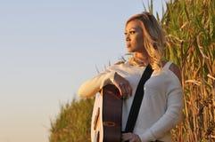 Schönheit mit Gitarre bei Sonnenuntergang Stockbild