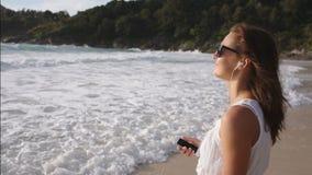 Schönheit mit Kopfhörern hörend Musik auf dem Strand stock video footage