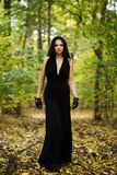 Schönheit mit langem schwarzem Kleid im Wald Lizenzfreies Stockbild