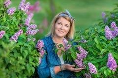 Schönheit mit lila Bündel und Kranz von Blumen arbeiten im Frühjahr, Porträt der jungen schwangeren Mutter im Garten Stockfoto