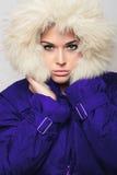 Schönheit mit Pelzhaube. modernes Mädchen des Winters im blauen Mantel Lizenzfreie Stockfotos