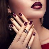 Schönheit mit perfektem Make-up und tragendem Schmuck Burgunders und der goldenen Maniküre stockfotografie