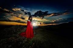 Schönheit mit rotem Mantel im Sonnenunterganglicht lizenzfreie stockfotos
