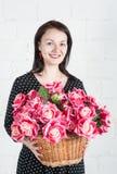 Schönheit mit roten Blumen im Korb lizenzfreie stockfotografie