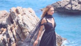 Schönheit mit schwarzem Schal im eleganten schwarzen Kleid stock footage