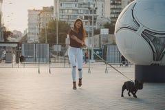 Schönheit mit schwarzem Welpen der französischen Bulldogge an der Straße stockfotografie