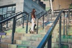 Schönheit mit schwarzem Welpen der französischen Bulldogge an der Treppe lizenzfreie stockfotos