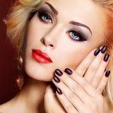 Schönheit mit schwarzen Nägeln und den roten Lippen Stockfotografie