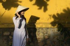 Schönheit mit Vietnam-Kulturtrachtenkleid und Holdinghut, AO Dai ist berühmtes traditionelles Kostüm, Weinleseart, Hoi lizenzfreie stockbilder