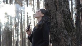 Schönheit raucht eine elektronische Zigarette in einem Park bei Sonnenuntergang stock footage