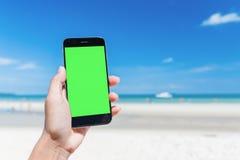 Schönheit ` s Hand unter Verwendung des intelligenten Telefons am Strand Stockfoto