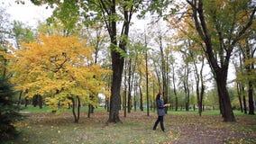 Schönheit sammelt einen Blumenstrauß von gefallenen Blättern im Herbstpark stock footage