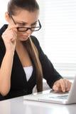 Schönheit sitzt bei Tisch und arbeitend auf Laptop lizenzfreies stockfoto