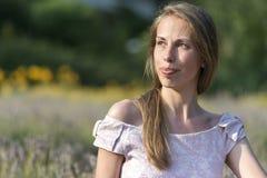 Schönheit am sonnigen Tag, der rosa Kleid trägt und auf neuem lavander Gebiet, Schönheit der Natur genießend sitzt Stockbild