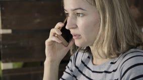 Schönheit spricht am Telefon mit der Konzentration stock footage