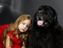 Schönheit und das Tier-Mädchen mit großem schwarzem Wasserhund Lizenzfreie Stockfotografie