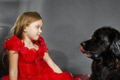 Schönheit und das Tier-Mädchen mit großem schwarzem Wasserhund Stockfotografie