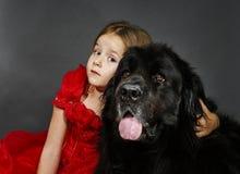 Schönheit und das Tier-Mädchen mit großem schwarzem Wasserhund Lizenzfreie Stockbilder
