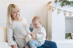 Schönheit und ihr Baby, die mit der Spielzeugkiste sitzt auf einem Sofa im Reinraum spielt Stockfoto