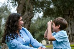 Schönheit und ihr netter kleiner Sohn, die einander, Sohn macht den Nachahmer vom Machen des Fotos der Mutter betrachtet lizenzfreies stockfoto