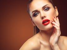 Schönheit vorbildliches Woman mit langem gewelltem Haar Browns Gesundes Haar und schönes Berufsmake-up Rote Lippen und rauchige A lizenzfreie stockfotografie