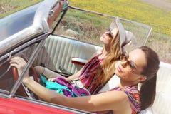 Schönheiten, die eine rote Retro- Weinlese des Autos tragende accesoriess fahren Lizenzfreie Stockfotografie