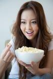 Schönheiten, die eine Schüssel Popcorn halten lizenzfreie stockbilder