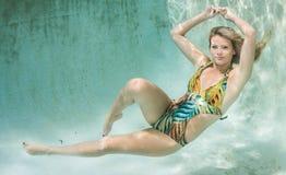Schönheiten in einem Badeanzug oder im Meerjungfrauendstück über und unter Stockfotos