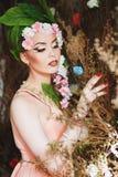 Schönheits-Frühlingsmädchen mit dem Blumenhaar Schöne vorbildliche Frau mit Blumen auf ihrem Kopf Die Art der Frisur Sommer Stockfotografie