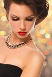 Schönheits-Frau mit perfektem Make-up und Luxuszubehör auf Goldhintergrund Stockfotos
